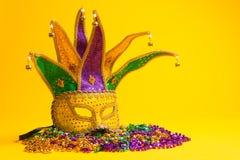 Colorful Mardi Gras or venetian mask on yellow. A festive, colorful mardi gras or carnivale mask on a yellow background. Venetian mask royalty free stock image