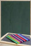Colorful markers pens on black board for text Royalty Free Stock Images
