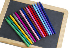 Colorful markers pens on black board for text Stock Photography