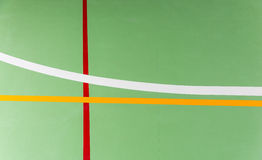 Colorful markings on an indoor sports court. Colorful markings on the green floor of an indoor sports court forming a striking abstract geometric design as they Stock Image