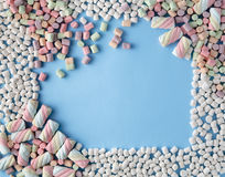 Colorful marshmallows candy frame on blue background Stock Photos