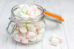 Colorful marshmallows in glass jar closeup. Colorful marshmallows in glass jar on light wooden background closeup Royalty Free Stock Images