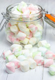 Colorful marshmallows in glass jar. On light background Royalty Free Stock Photos