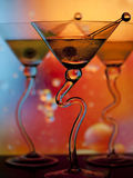 Colorful martinis. Three martinis in glasses with curved stems in front of colorful lighted background Royalty Free Stock Image