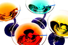 Colorful martinis. A row of colorful martinis on white Royalty Free Stock Images