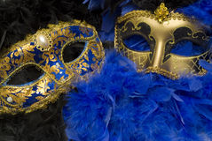 Colorful masks. On black and blue feather boas Stock Image