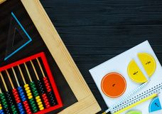 Colorful math fractions on dark wooden background or table. Interesting math for kids. Education, back to school concept. Geometry. And mathematics materials royalty free stock image