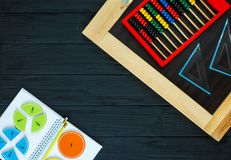 Colorful math fractions on dark wooden background or table. Interesting math for kids. Education, back to school concept. Geometry. And mathematics materials royalty free stock photography