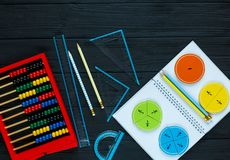 Colorful math fractions on dark wooden background or table. Interesting math for kids. Education, back to school concept. Geometry and mathematics materials stock image