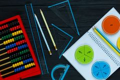 Colorful math fractions on dark wooden background or table. Interesting math for kids. Education, back to school concept. Geometry and mathematics materials stock photography