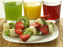 Colorful meal. Plate of fruit shashlik and glasses with juice stock photo