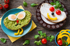 Colorful meal for kids: healthy vegetable sandwiches. Funny colorful creative meal idea for kids: avocado sandwich with hard boiled egg, pepper nose and black Stock Photos