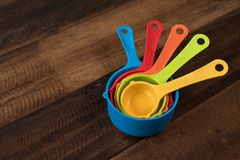 Colorful measuring cups on a wooden table stock photo