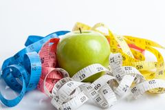 Colorful measuring tapes with green apple Stock Images