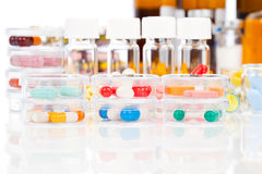 Colorful medical capsules in Petri dishes. Royalty Free Stock Photos