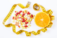 Colorful medical pills, fresh orange and centimeter on white background, health care, healthy lifestyle and slimming concept Stock Photo