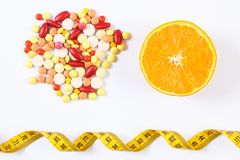 Colorful medical pills, fresh orange and centimeter on white background, health care, healthy lifestyle and slimming concept Royalty Free Stock Photo