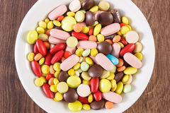 Colorful medical pills, tablets and capsules on plate, health care concept Stock Images