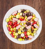 Colorful medical pills, tablets and capsules on plate, health care concept Stock Image