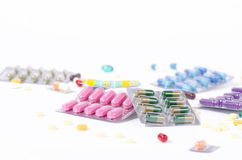 Colorful medicine in blister packs. Top view colored medicine in transparent blister packs with scattered pills in the background Royalty Free Stock Photo
