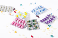 Colorful medicine in blister packs. Top view colored medicine in transparent blister packs with scattered pills in the background Royalty Free Stock Photos