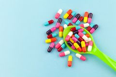 Colorful medicine capsules. With spoon  on blue background Royalty Free Stock Photo
