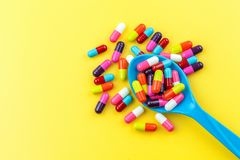 Colorful medicine capsules. With spoon  on yellow background Royalty Free Stock Photos