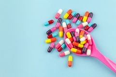 Colorful medicine capsules with spoon. On blue background Royalty Free Stock Image