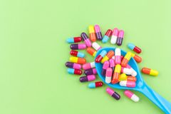 Colorful medicine capsules with spoon. On green background Stock Photos