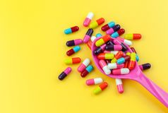 Colorful medicine capsules with spoon. On yellow background Royalty Free Stock Photos