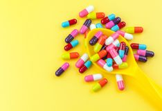 Colorful medicine capsules with spoon. On yellow background Royalty Free Stock Images