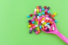 Colorful medicine capsules with spoon. On green background Royalty Free Stock Photos