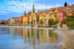 Colorful medieval town Menton on Riviera, Mediterranean sea, Fra. Sand beach beneath the colorful old town Menton on french Riviera, France Royalty Free Stock Image