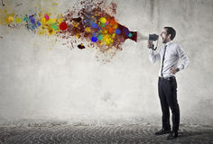 Colorful megaphone. Business man is  speaking to a megaphone and paint comes from it Stock Photography
