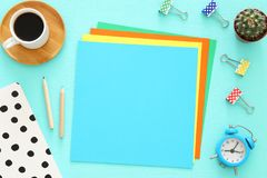 Colorful memo empty pages and other office supplies over mint blue office desk table. Top view. Stock Photos