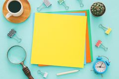 Colorful memo empty pages and other office supplies over mint blue office desk table. Top view. Stock Images