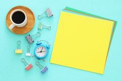 Colorful memo empty pages and other office supplies over mint blue office desk table. Top view. Royalty Free Stock Photography