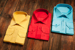 Colorful men's shirts on a wooden background Royalty Free Stock Image