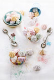 Colorful meringue cookies over white wooden background Royalty Free Stock Images