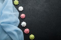 Colorful meringue on a dark table. Fashionable air dessert for Valentine`s Day. Copy space stock photography