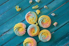 Colorful meringues on wooden background Stock Images