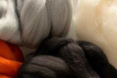 Merino wool, white, black, red and gray colors, for felting, close up. Colorful merino wool, white, black, red and gray colors, for felting, close up Stock Image