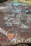 Messages on a boulder. Colorful messages on a large boulder with different meanings stock photos