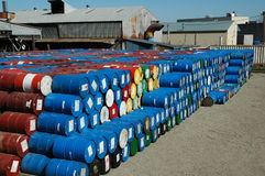 Colorful Metal Drums. Large pile of different color metal storage drums behind industrial buildings Stock Photos