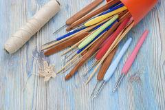 Colorful metal and wooden natural bamboo crochet hooks and needles on the table. Various sizes. Creative work place for homemade c Royalty Free Stock Photography