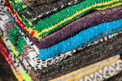 Colorful Mexican serapes hang in row. Mexican serape fabric colorful pattern texture background Royalty Free Stock Image
