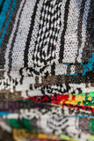 Colorful Mexican serapes hang in row. Mexican serape fabric colorful pattern texture background Royalty Free Stock Photo