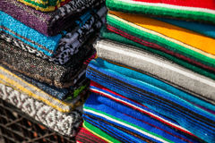 Colorful Mexican serapes hang in row. Mexican serape fabric colorful pattern texture background Stock Photography