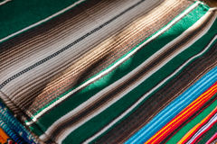 Colorful Mexican serapes hang in row. Mexican serape fabric colorful pattern texture background Royalty Free Stock Images