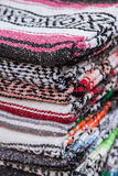 Colorful Mexican serapes hang in row. Royalty Free Stock Images